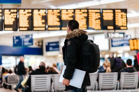 man in parka looking at flight schedule in airport